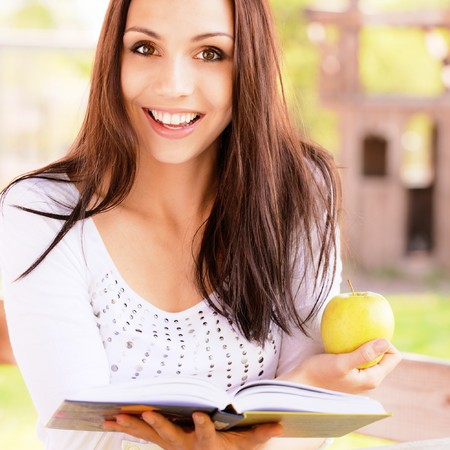 Charming long-haired girl reads book photo