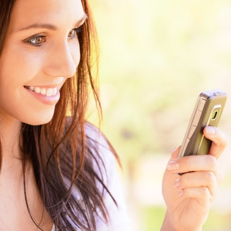 Lovely young woman reads sms on mobile phone photo
