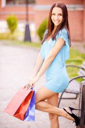 Young smiling woman with multi-colored packages is glad to purchases.