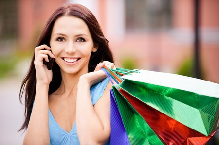 talks: Young smiling woman to purchases talks on cellular telephone.