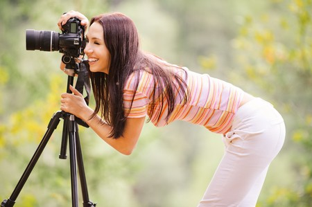 tripod: Beautiful smiling girl with camera on nature.