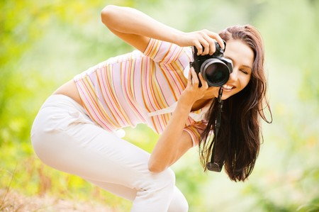 Beautiful smiling girl with camera on nature.
