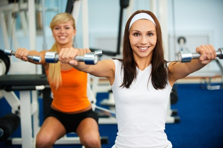 portrait of two girls working out with dumbbells photo