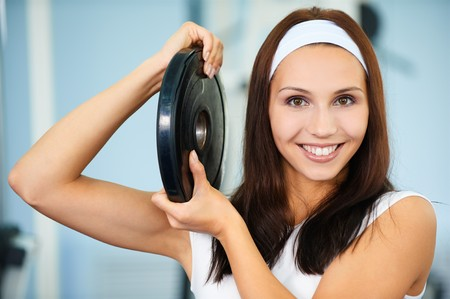 portrait of sporty girl posing with single weight photo