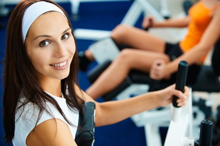 portrait of girl exercising in gym. other girl on multi gym out of focus on background.