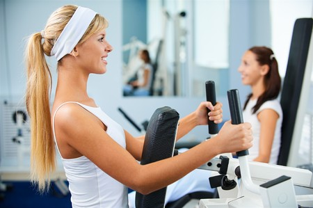 fitness club: portrait of two girls exercising in gym on various machines