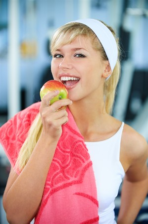 portrait of happy sporty blonde girl eating apple in gym Stock Photo - 7657903