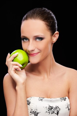 portrait of beautiful brown-haired girl with green apple on black photo