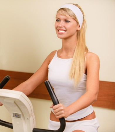Sportgirl go in for sports on velosimulator. photo
