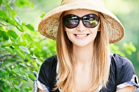 Young beautiful girl in straw hat against city park. photo