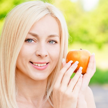 Beautiful blonde with red apple against summer nature. photo