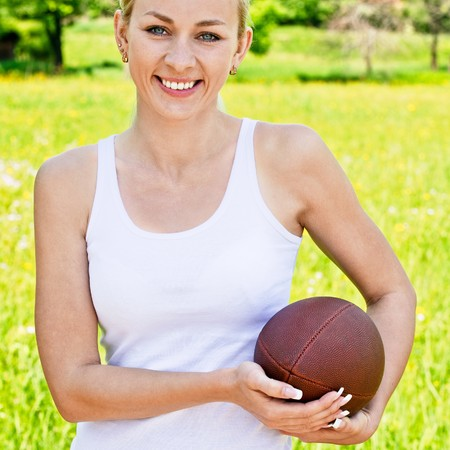 Portrait of sportswoman of Rugby football against green summer nature.