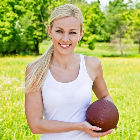 sportwoman: Portrait of sportswoman of Rugby football against green summer nature.