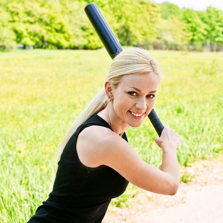 Sportswoman with baseball bat against summer city park. photo