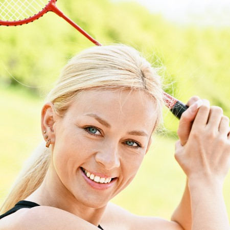 Sportswoman plays badminton against summer city park. Stock Photo - 7785609