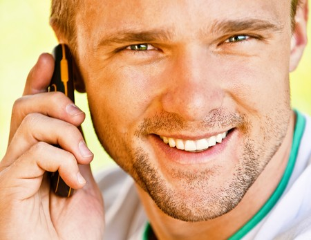 Young man smiles and speaks on phone, close up. photo