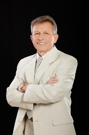 portrait of senior handsome businessman in white suit on black photo