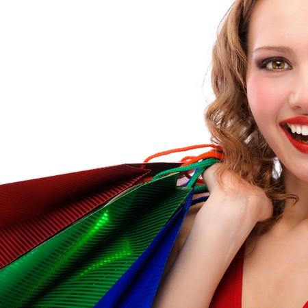 La mitad de cara de ni�a de regocijo en un vestido rojo con las compras, aislado sobre fondo blanco.  Foto de archivo - 7810932