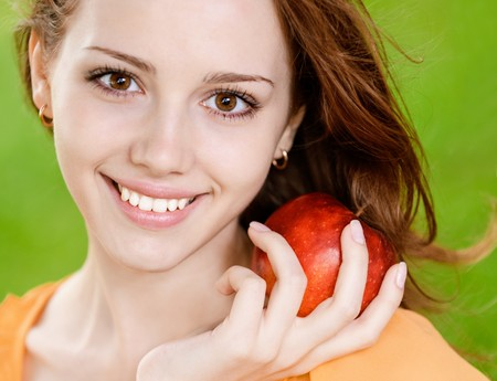 Portrait of girl with red apple against green grass. photo