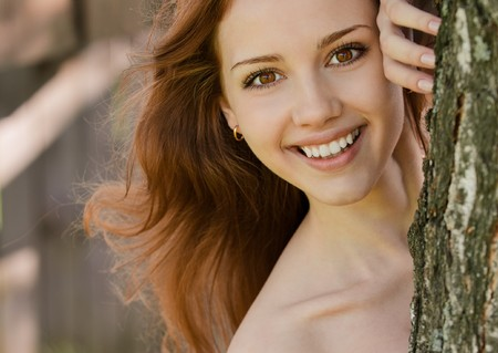 bared teeth: Portrait of smiling young woman looks out because of tree. Stock Photo