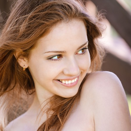 Portrait of laughing young woman with bared shoulders.