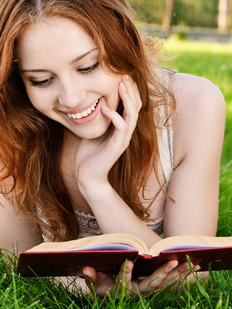 Charming girl reads book on green grass. photo