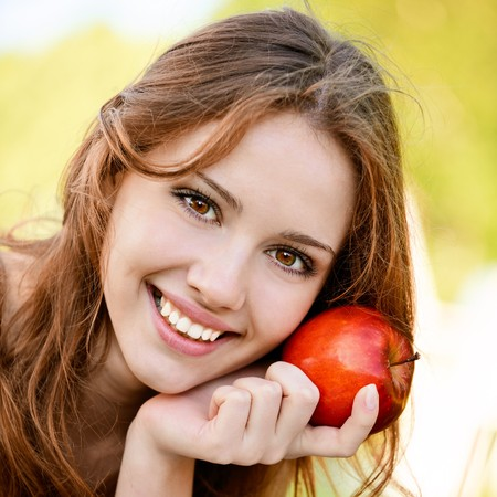 and lies: Charming girl with apple lies on green grass.