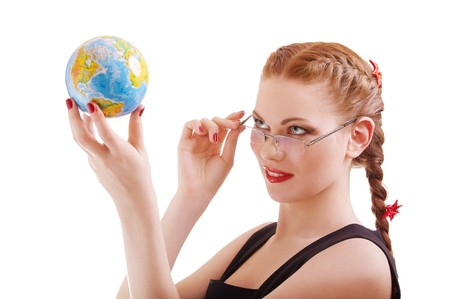 portrait of red-haired girl in glasses with globe in her hands on white photo