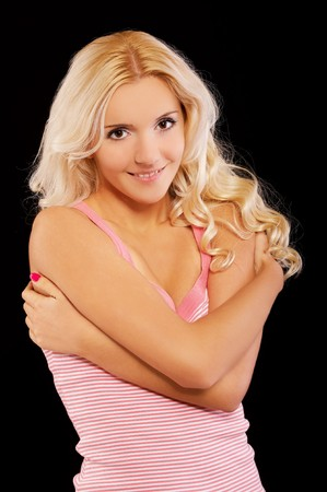 portrait of beautiful blonde in pink striped tank top posing on black photo