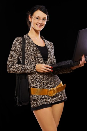 portrait of beautiful brunette in glasses and leopard dress with laptop on black photo