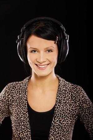 portrait of beautiful brunette in headphones on black photo