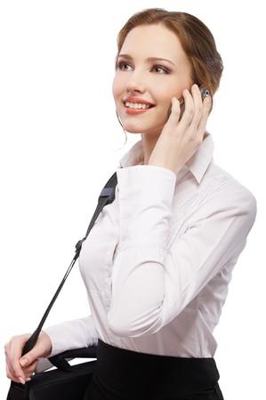 pelirrojas: Retrato de una hermosa chica pelirroja en una blusa blanca con bolsa de port�til haciendo llamadas telef�nicas  Foto de archivo
