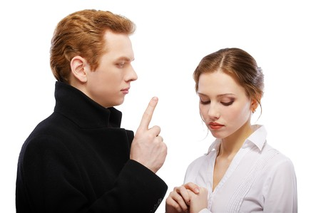 rigorous: portrait of red-haired couple. man is shaking finger and girl is looking guilty. Stock Photo