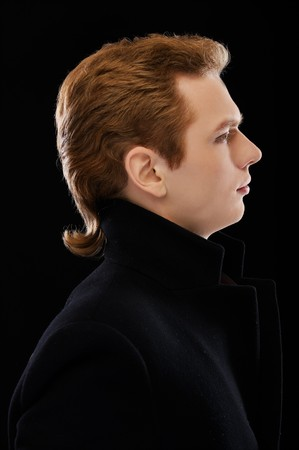 portrait of handsome red-haired guy on black photo