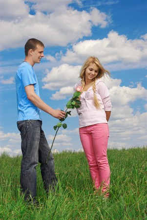 young couple outdoor on green grass. guy granting flower, girl looking shy. blue sky with clouds on background. photo