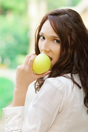 portrait of beautiful brunette girl with yellow apple photo