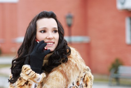 portrait of beautiful brunette in furs speaking over cellphone outdoors photo