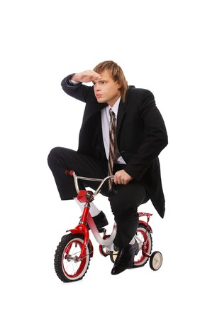portrait of businessman riding on childs bicyce and looking forward photo