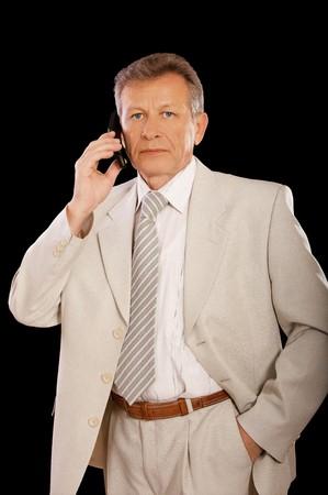 portrait of senior businessman in suit speaking over cellphone on black photo