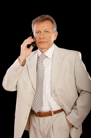 portrait of senior businessman in suit speaking over cellphone on black photo