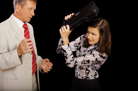 concept portrait of senior handsome businessman attacking younger businesswoman who is protecting herself with leather black case photo