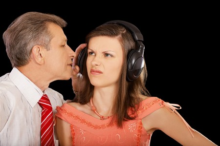 to interfere: expression family portrait of senior man pulling of headphone from offended girls head