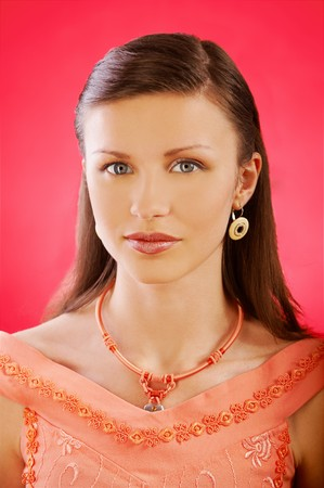 portrait of pretty brown-haired girl with ear-rings and necklace on red photo