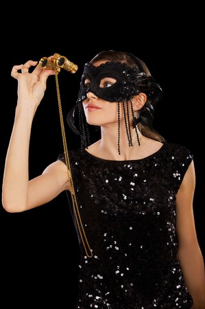 portrait of girl in mask and black shiny dress with theatrical binocular photo