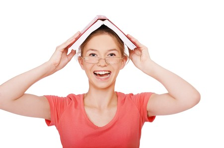 expression portrait of happy smart girl student in glasses holding book on her head like roof on white photo