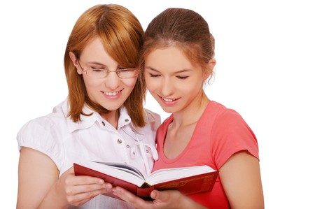 isolated portrait of two happy student girls reading the book photo