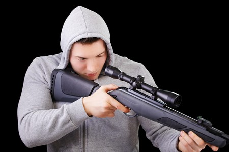 portrait of handsome young man in gray jacket with hood aiming the sniper rifle on black photo