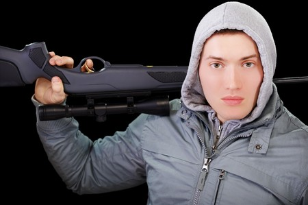 portrait of handsome young man in gray jacket with hood holding sniper rifle in hands on black photo