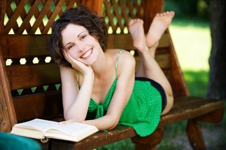 scalzo ragazze: esterno ritratto di giovane donna felice bella posa sul banco e libro di lettura nel parco