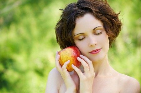 shut: outside portrait of beautiful young curly woman with eyes shut with red apple in park